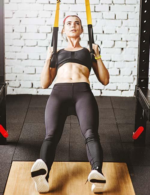 Девушка делает упражнение на TRX