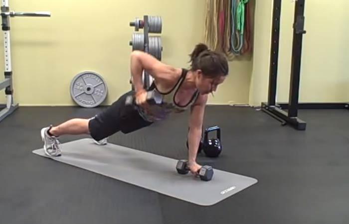 Девушка делает упражнение с гантелями