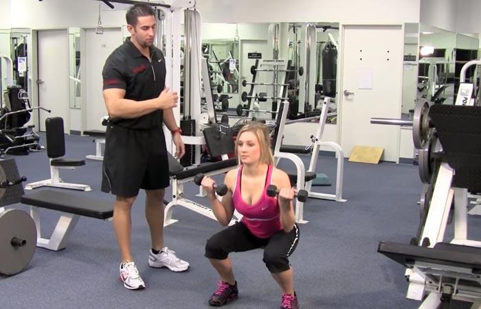 Девушка приседает в спортзале